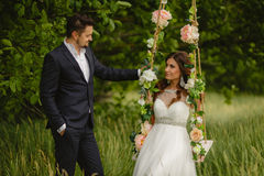 Beautiful bride with fiance is swinging on a swing Royalty Free Stock Images