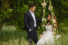 Beautiful bride with fiance is swinging on a swing Royalty Free Stock Photo