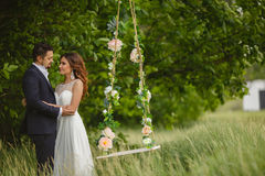 Beautiful bride with fiance is swinging on a swing Royalty Free Stock Image