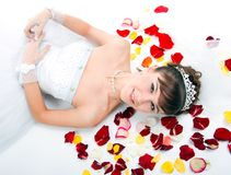 Beautiful  bride on  floor among red rose petals Royalty Free Stock Photography