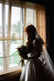 Beautiful bride with flower bouquet. Standing near window Stock Photo