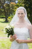 Beautiful bride with flower bouquet wearing veil Royalty Free Stock Image
