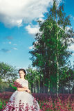 Beautiful bride in a flower field. The girl in a white dress with a bouquet in a summer field at sunset Royalty Free Stock Images