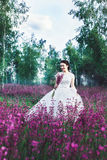 Beautiful bride in a flower field. The girl in a white dress with a bouquet in a summer field at sunset Royalty Free Stock Photography