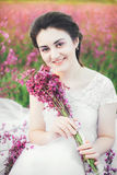 Beautiful bride in a flower field. The girl in a white dress with a bouquet in a summer field at sunset Royalty Free Stock Image