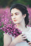 Beautiful bride in a flower field. The girl in a white dress with a bouquet in a summer field at sunset Stock Photo