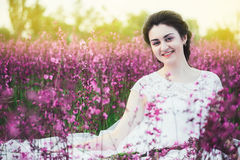 Beautiful bride in a flower field. The girl in a white dress with a bouquet in a summer field at sunset Stock Image
