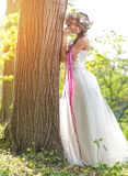 Beautiful bride , flower tiara on her head , relying on the tree.  Stock Photos