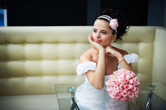 Beautiful bride with flowers on modern interior Royalty Free Stock Photos