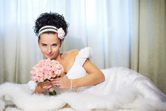 Beautiful bride with flowers on white bed Royalty Free Stock Photo