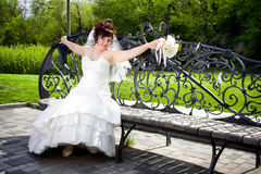 Beautiful Bride forged a bench and a bouquet Royalty Free Stock Photos