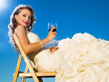 Beautiful bride in front of the blue sky. Beautiful bride is sitting with glass of red wine in front of the blue sky Royalty Free Stock Images