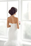 Beautiful bride in front of a window. Portrait of a beautiful  looking at window shot from behind Stock Photography