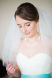Beautiful bride getting dressed on the wedding day Stock Photo