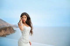 Beautiful bride girl in beaded wedding dress. Summer holiday fas. Hion concept. Luxury resort woman posing by infinity swim pool over blue sky with sea stock photography
