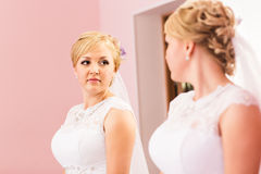 Beautiful bride girl  with hairstyle and bright makeup looks in the mirror Royalty Free Stock Image