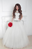 Beautiful bride girl with red roses bouquet posing in modern int Stock Images