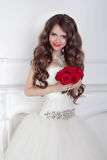 Beautiful bride girl with red roses bouquet posing in modern int Royalty Free Stock Images