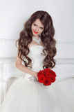 Beautiful bride girl with red roses bouquet posing in modern int Stock Photos