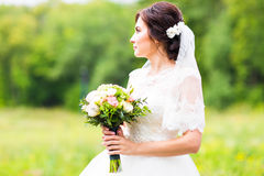 Beautiful bride girl in wedding dress with bouquet of flowers, outdoors portrait Royalty Free Stock Images
