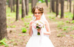 Beautiful bride girl in wedding dress  and bouquet of flowers, outdoors portrait Royalty Free Stock Photos