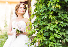 Beautiful bride girl in wedding dress  and bouquet of flowers, outdoors portrait Stock Images