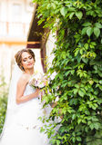 Beautiful bride girl in wedding dress  and bouquet of flowers, outdoors portrait Royalty Free Stock Photography