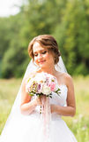 Beautiful bride girl in wedding dress  and bouquet of flowers, outdoors portrait Stock Image