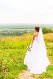 Beautiful bride girl in wedding dress  and bouquet of flowers, outdoors portrait Stock Photo