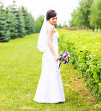 Beautiful bride girl in wedding dress with bouquet of flowers, outdoors portrait Stock Photos