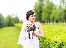 Beautiful bride girl in wedding dress with bouquet of flowers, outdoors portrait Royalty Free Stock Photography