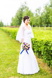 Beautiful bride girl in wedding dress with bouquet of flowers, outdoors portrait Stock Images