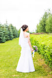 Beautiful bride girl in wedding dress with bouquet of flowers, outdoors portrait.  Royalty Free Stock Photo