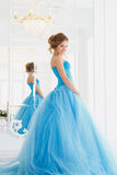 Beautiful bride in gorgeous blue dress Cinderella style near mirror royalty free stock photo