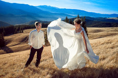 Beautiful bride gracefully dances before her groom on the field. Honeymoon in Alps Stock Images