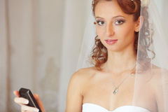 Bride with the phone. Beautiful bride graduated prazgovor on mobile phone and puzzled looks stock photography