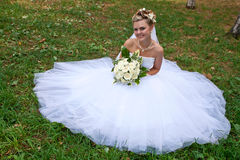 Beautiful bride on grass. Beautiful smiling bride  sitting on the grass in a park Royalty Free Stock Images