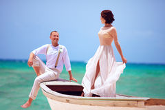 Beautiful bride and groom in boat swimming at caribbean sea Stock Photos