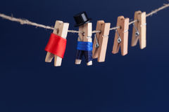 Beautiful bride and groom clothespin toys on clothesline. Abstract woman in red wedding dress and man with suit black. Hat. Love concept photo. Macro view Royalty Free Stock Image