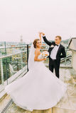 Beautiful bride and groom dancing on the terrace with cityscape background Royalty Free Stock Photo