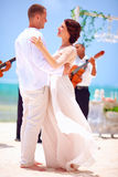 Beautiful bride and groom dancing on tropical beach Stock Photography