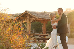 Beautiful bride and groom embracing at dusk Stock Photography