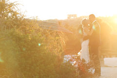 Beautiful bride and groom embracing at dusk Stock Images