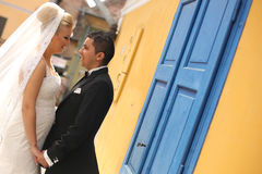 Beautiful bride and groom embracing near colorful door and wall Stock Image