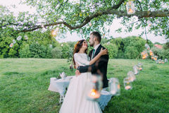 Beautiful bride and groom in evening park embracing under tree decorated with many lanterns Royalty Free Stock Photography