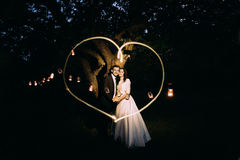 Beautiful bride and groom in evening park holding each other under tree decorated with many lanterns. Lightpainted heart Royalty Free Stock Image
