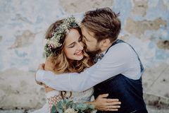 Beautiful bride and groom in front of old shabby house. stock photos