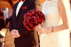 Beautiful bride and groom. Holding red flowers bouquet in hands Stock Photos