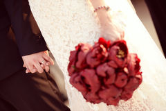 Beautiful bride and groom. Holding red flowers bouquet in hands Royalty Free Stock Photography