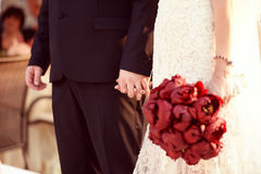 Beautiful bride and groom. Holding red flowers bouquet in hands Stock Image